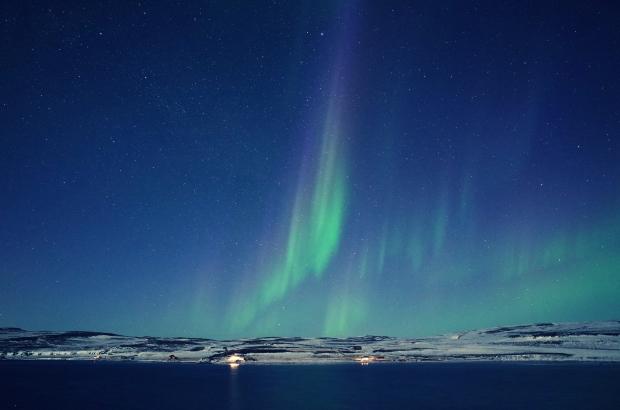 極光在對岸綻放著漸層變化的顏色, 從粉紅到綠